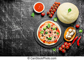 Raw pizza. Dough with tomato paste, mushrooms, olives and chili pepper.