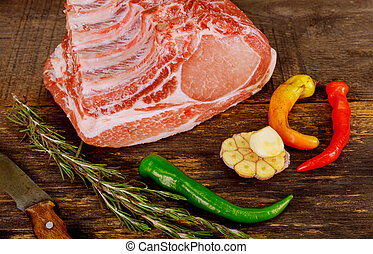 Raw pork meat tenderloin with herb on wooden background.