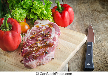 Raw pork on cutting board and vegetables knives.