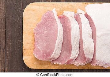 Raw pork on cutting board on wooden background.