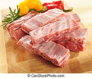 Raw pork ribs. Arrangement on a cutting board. - Raw pork...