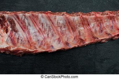 Raw pork ribs on black stone background,