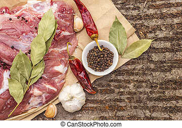 Raw pork shoulder with spices. Bay leaf, garlic, chili. On a wooden bark background, close up, top view.