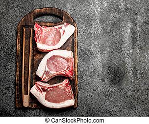 Raw pork steaks on a cutting Board.