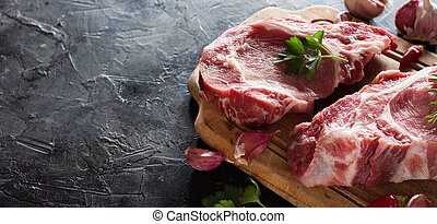 Raw pork steaks called  capicola with vegetables and herbs