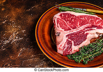 Raw porterhouse beef meat Steak with herbs on a plate. Dark background. Top view. Copy space