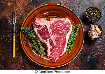 Raw porterhouse beef meat Steak with herbs on a plate. Dark background. Top view
