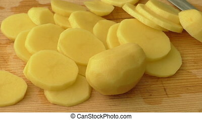 Raw potatoes and knife on a wooden background