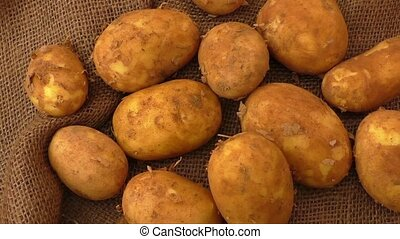 Raw potatoes on rustic hessian background