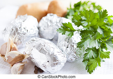 Raw potatoes wrapped in foil, food close-up