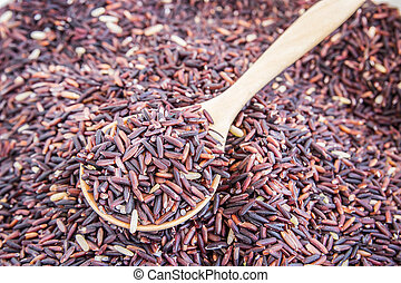 Raw purple rice berry in wooden spoon