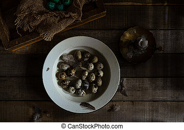 Raw quail eggs and feathers, some colored eggs on wooden rustic background. Dark Moody Still Life Photography
