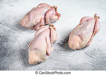 Raw quails on a kitchen table. White background. Top view