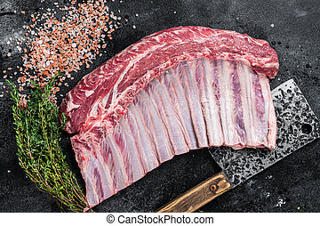 Raw rack of lamb ribs on butcher cutting board with herbs. Black background. Top view