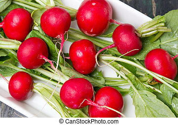 Raw radishes with leaves in a bowl