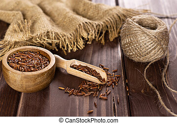 Composition of lot of whole raw red rice with wooden bowl on brown wood