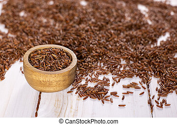 Lot of whole raw red rice with wooden bowl on white wood