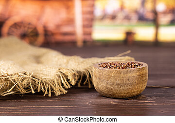 Lot of whole raw red rice jute cloth with wooden bowl with cart in background