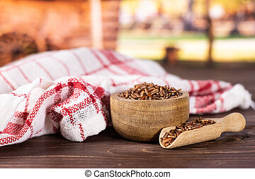 Lot of whole raw red rice tea towel with wooden bowl with cart in background