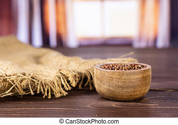 Lot of whole raw red rice jute cloth with wooden bowl with silk curtains behind
