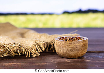 Lot of whole raw red rice jute cloth with wooden bowl with green wheat field in background