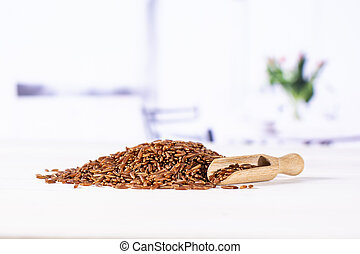 Lot of whole raw red rice with wooden scoop with red flowers on white in background
