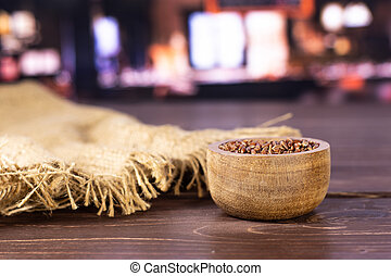 Lot of whole raw red rice jute cloth with wooden bowl with restaurant in background