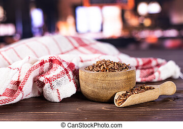 Lot of whole raw red rice tea towel with wooden bowl with restaurant in background