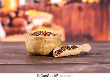 Lot of whole raw red rice in a scoop with wooden bowl with rustic wood kitchen in background