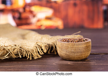 Lot of whole raw red rice jute cloth with wooden bowl with rustic wood kitchen in background