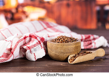 Lot of whole raw red rice tea towel with wooden bowl with rustic wood kitchen in background