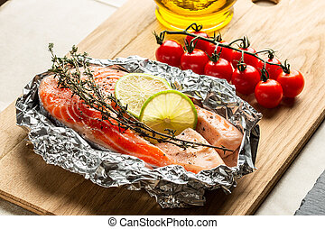 Raw red salmon and cherry tomatoes on the wooden cutting board