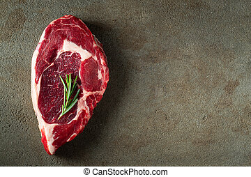 Raw ribeye beef steak with herbs and spices on a brown concrete background. Top view. Flat lay.
