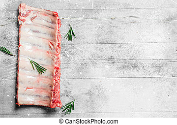 Raw ribs with rosemary branches .
