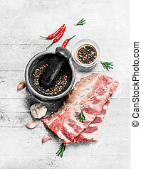 Raw ribs with spices and rosemary .