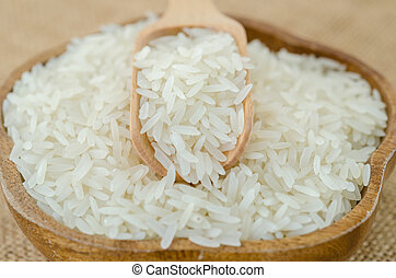 Raw rice and wooden spoon in wooden bowl.