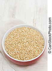 raw rice in red bowl on wooden background