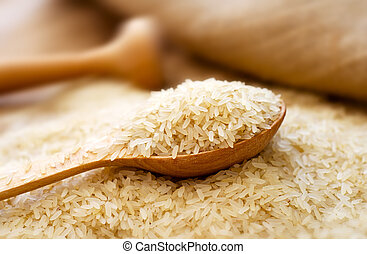 Raw rice in the wooden spoon