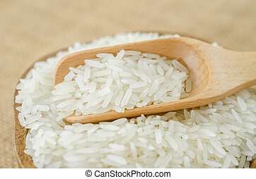 Raw rice in wooden bowl with wooden spoon.