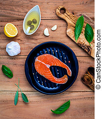 Raw salmon fillet in the black plate
