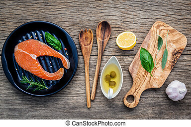 Raw salmon fillet in the black plate with ingredients