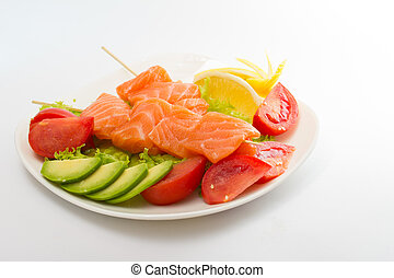 raw salmon fillet on sticks with vegetables