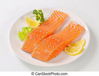 Raw salmon fillets and lemon on plate
