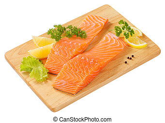 Raw salmon fillets on cutting board