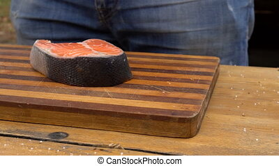 Raw salmon fish steak preparation for outdoor barbeque