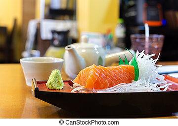 Raw salmon slice sashimi on ice Japanese style in restaurant.