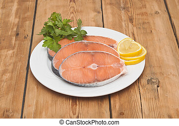 raw salmon steak on white dish over wooden table