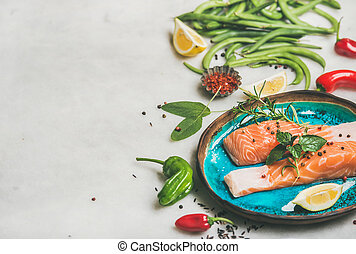 Raw salmon steaks with vegetables, greens, rice in blue...