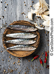 raw sardines on a rustic wooden table - high angle view of...