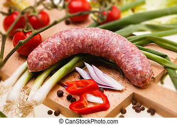raw sausage with vegetables on wooden board